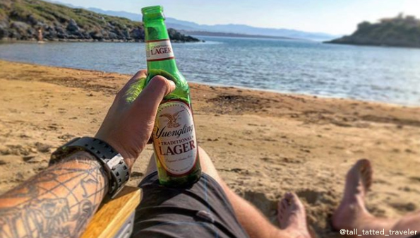 A fan photo holding a Yuengling on a beach