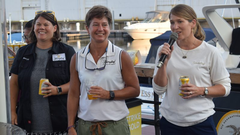 Sheryl, Jen and Wendy Yuengling holding Golden Pilsner and speaking to a crowd