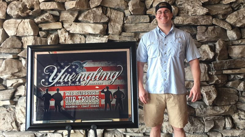 Scholarship recipient standing next to a patriotic Yuengling sign